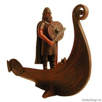 Viking figur stående i stavnen på vikingskip med skjold og vikingsverd